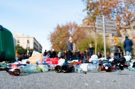 Barcelona, Spain - 21 december 2018: stack of glass and plastic waste lay on asphalt street during sunny day Sajtókép