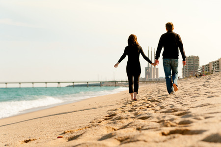 young happy pregnant couple walking together bare feet at the beach holding hands dressed in dark clothes during sunny day
