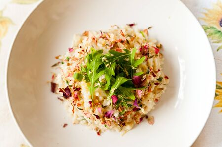 delicious italian homemade risotto on table cloth with arugula salad lemon and edible flowers and soft natural light