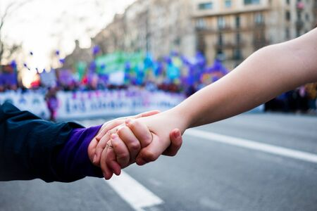 young women holding hands during woman's day rally with purple balloons in background for women rights and feminism