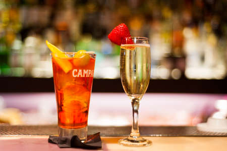 Barcelona, Spain - 20 april 2019: glass of aperol campari spritz and spanish wine cava with strawberry on bar top in a nightclub