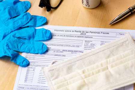 Barcelona, Spain - 20 april 2020: close up of impuesto sobre la renta form for spanish tax declaration with gloves and face mask as a symbol of coronavirus and spanish economy Editorial