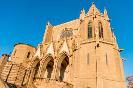front facade view of Collegiate Basilica of Santa Maria Seu in Manresa city in catalunya region in Spain, with trees and clear blue sky during sunny autumn day at sunset Editorial