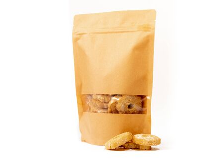 brown craft food packaging in paper, plain doypack standup bag filled with biscuits with window and zipper on white background