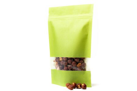 green paper doy pack standup pouch filled with hazelnuts with window and zipper front view on white background Foto de archivo