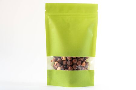 green food packaging in paper, doypack standup bag filled with hazelnut with window and zipper on white background Foto de archivo