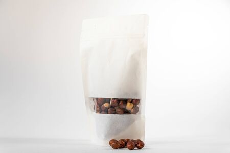 white paper doypack eco friendly food package filled with hazels with window and zipper on white background Foto de archivo - 148519307