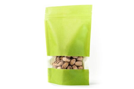 green paper standup pouch filled with dry fruit, flexible packaging with window zipper on white background Foto de archivo