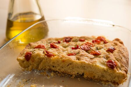 close up of italian focaccia genovese, a traditional italian food with warm and natural light and olive oil, and tomato cherry and rosemary on top Foto de archivo