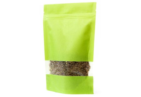 green spices and herbs packaging in paper, plain doypack standup bag filled with dry herbs with window and zipper on white background