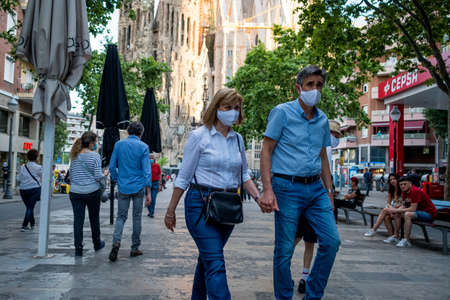 Barcelona, Spain - 20 may 2020: tourists wearing face mask walk in the european city during the corona virus pandemic. The travel and tourism industries are the more badly hit by the crisis