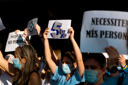 Barcelona, Spain - 20 may 2020: nurses protest during corona virus crisis, for the lack of personnel and pay cuts, wearing face mask in front of hospital Editorial