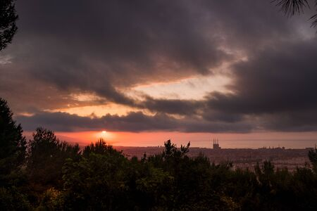 dramatic sunrise view of barcelona at dusk from guinardo park, with sun rising through clouds and cityscape with tres xemeneies