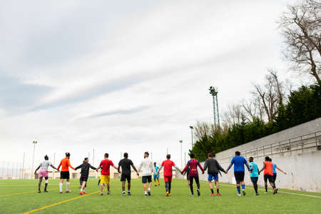 Barcelona, spain - 20 june 2020: a mixed race football team during practice holding hands, creating community and social inclusion with migrant young players