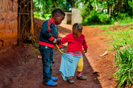 Bafoussam, cameroon - 20 august 2019: a young african boy helps his sister dress up, an example of support and respect and brotherhood in the family Foto de archivo - 150387827
