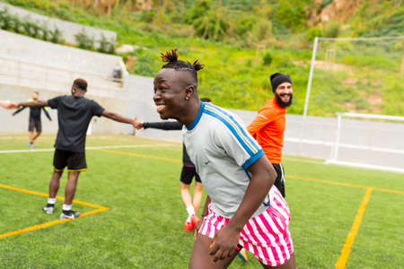 Barcelona, spain - 10 june 2020: portrait of young african black immigrant man playing soccer in team, smiling and enjoying together with teammates in pitch, football is a tool for social inclusion