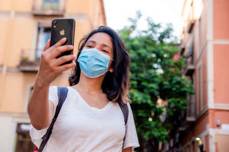 young tourist woman taking selfie with face mask, example of tourism industry at the time of covid19. symbol of summer holidays at the time of corona virus Foto de archivo