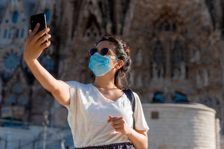 young tourist woman taking selfie with face mask in front of sagrada familia landmark of barcelona in spain, tourism industry crisis at the time of covid19. symbol of summer holidays
