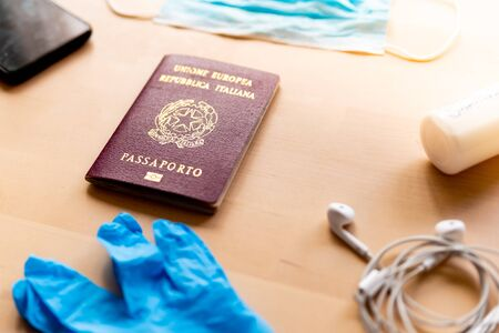 corona virus travel and tourism concept, italian passport and face mask as symbol of the traveling industry crisis and the new safety measures after the virus global outbreak Foto de archivo - 150410550