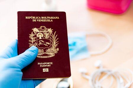 close up of hands with medical gloves holding passport, a symbol of the new border checks following the coronavirus spread and globla contagion. the travel and tourism industries face a big issue due to lockdowns Foto de archivo