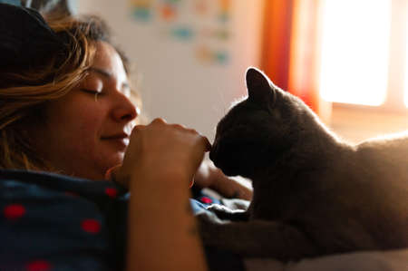 young woman relaxing in bed with her cat pet, a lazy cozy sunday morning scene, giving love to her companion smiling Foto de archivo