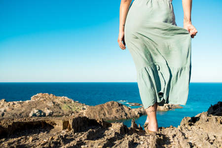 young, brave woman standing on top of rock on a summer day watching epic sea landscape with dress moving in the wind , evocative and inspiring back view of fearless person Foto de archivo - 151369949