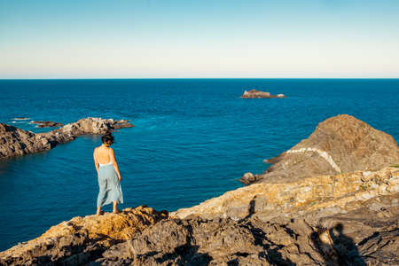 young determined woman standing on top of rocky cliff on the sea at sunset, reflecting and meditating in the blowing wind Foto de archivo