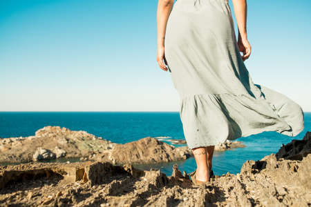 young, brave woman standing on top of rock on a summer day watching epic sea landscape with dress moving in the wind , evocative and inspiring back view of fearless person Foto de archivo