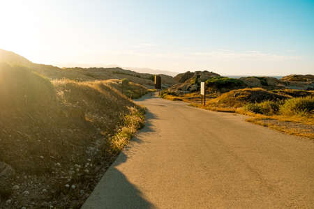 empty rocky and curvy road among virgin, wild landscape at sunset, a path and symbol and life, choices and growth Foto de archivo - 151395218