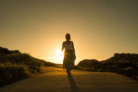 young determined woman silhouette walking against the sunset with sunrays, a beautiful evocative scene, symbol of following your own path and destiny Foto de archivo