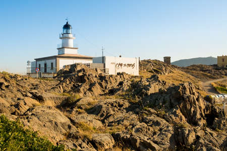 view of cap de creus lighthouse, a beacon of light on the rocky catalan costa brava, on a sunny summer day at sunset with warm light and wind blowing