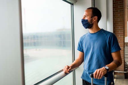 young man wearing protective face mask, traveling in the time of covid19 pandemic inside an airport, looking out of window with worried and upset expression. corona virus and travel industry
