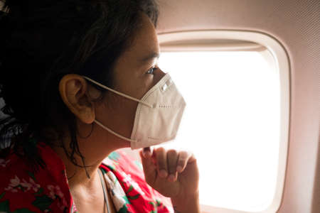 worried young woman inside plane wearing protective face mask, going on vacation and traveling during the coronavirus pandemic, which has caused a crisis in the travel and aviation industry Foto de archivo