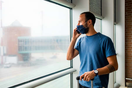 young man talking on the phone wearing protective face mask, traveling in the time of covid19 pandemic inside an airport, looking out of window with worried and upset expression