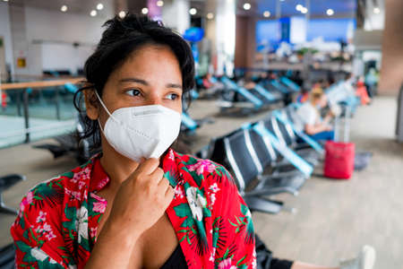 worried young woman inside airport wearing protective face mask with upset expression, travelling in the time of the covid pandemic, which has caused major flights disruption and crisis