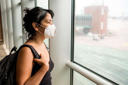 worried young woman at airport wearing face mask, going on vacation and traveling during the covid19 pandemic. Corona virus has caused a crisis in the travel and aviation industry Foto de archivo