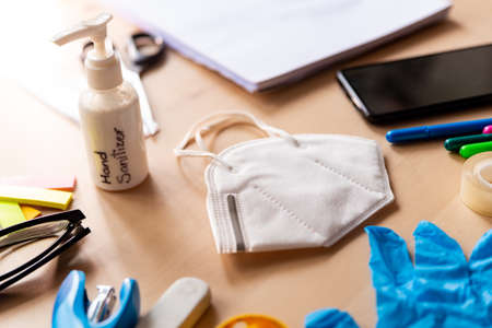 close up of face mask and hand sanitizer on wooden desk in class with mobile phone and block notes and education equipment. concept of prevention of covid-19 at school