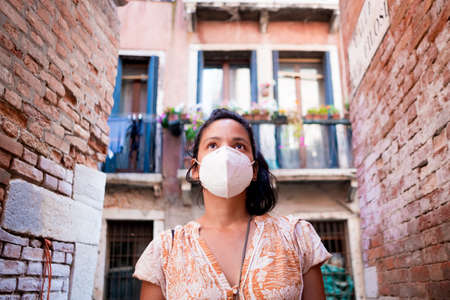 young tourist wearing face mask walking in a street of Venice in Italy. traveling and tourism industry during the corona virus pandemic and covid19 disease, affected by the global crisis