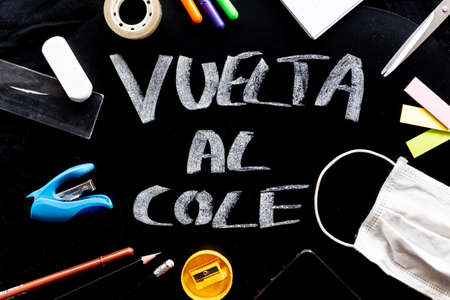 Vuelta al cole text in spanish, meaning back to school, with covid face mask on desk in classroom and stationery equipment. concept of education as a mayor issue in the time of corona virus