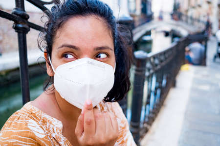 young woman with surgical mask sitting in a street of Venice in Italy. traveling and tourism industry during the coronavirus pandemic and covid19 virus, affected by the global crisis Foto de archivo