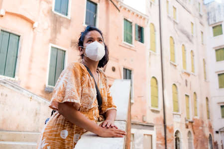 young tourist wearing face mask going around in a street of Venice in Italy. traveling and tourism industry during the corona virus pandemic and covid19 disease, affected by the global crisis Foto de archivo