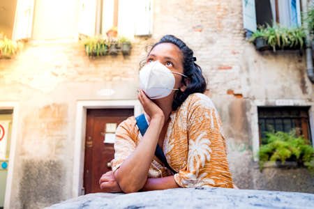 young woman wearing face mask looking up in a street of Venice in Italy. traveling and tourism industry during the corona virus pandemic and covid19 disease, affected by the global crisis Foto de archivo