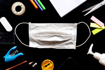 face mask on black desk in classroom with crayons and block notes and education equipment. concept of prevention of mayor issue in the time of corona virus