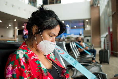 Barcelona, Spain - 20 august 2020: young woman inside airport wearing protective face mask with upset expression, travelling in the time of the covid pandemic, which has caused major flights disruption and crisis