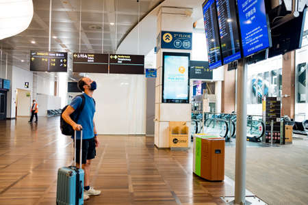 Barcelona, Spain - 20 august 2020: traveller with face mask at the airport with trolley, looking at flights schedule, alone in empty space, travelling in the time of corona virus