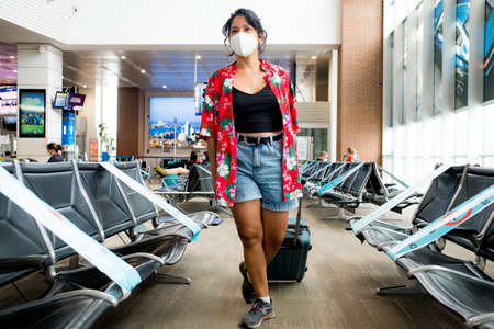 Barcelona, Spain - 20 august 2020: young woman walking inside airport wearing protective face mask with happy and positive attitude with trolley, holidays during the covid19 pandemic