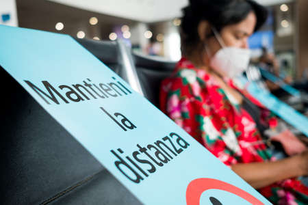 Venice, Italy - 20 august 2020: social distance sign in italian language with young woman sitting alone inside airport with face mask, traveling in the time of coronavirus