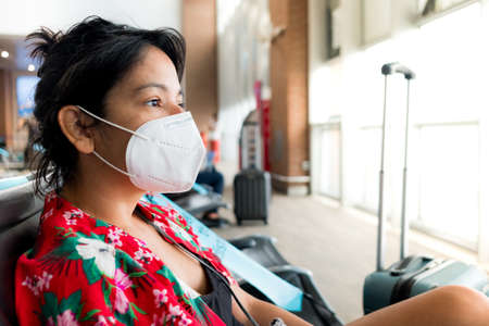 Barcelona, Spain - 20 august 2020: young woman traveller inside airport wearing protective face mask with upset expression, travelling in the time of the covid pandemic