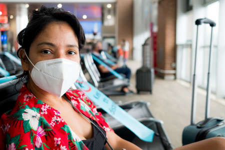 Barcelona, Spain - 20 august 2020: a young woman sit inside airport with face mask, looking in camera, going on holidays during a coronavirus global pandemic