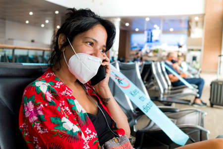 Barcelona, Spain - 20 august 2020: a young woman sit inside airport with face mask, talking on the phone travelling, during a coronavirus global pandemic